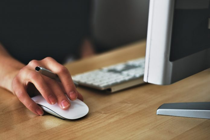 A hand holding a mouse click to surf the internet. apple-business-click