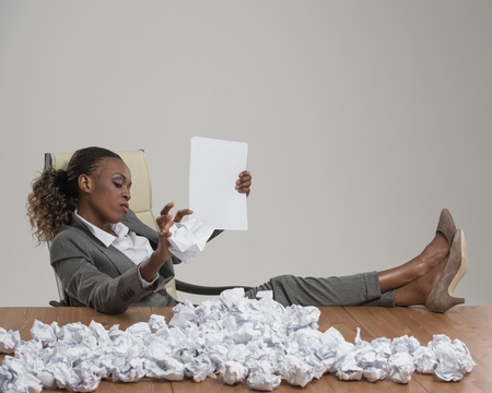 African business woman looking for workers . She is unhappy with cv of applicants and throwing crumpled papers with resume applications on table