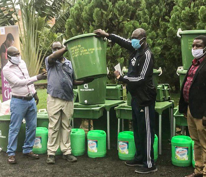 Dennis Adika (far right) looks on as governor Rasanga receives the hand washing units from West Kenya Sugar representative Sammy Ndeda.