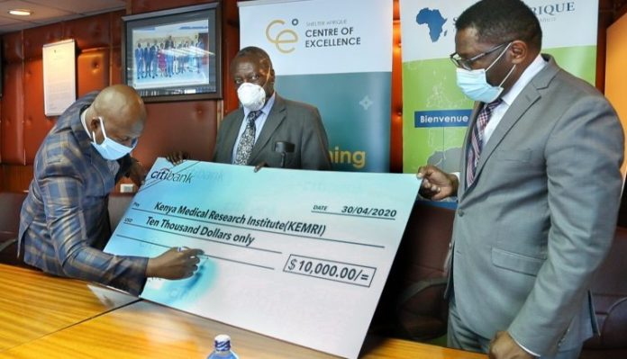 Shelter Afrique Chief Executive Officer Andrew Chimphondah (left) signs a Ksh 1,000,000 (USD10, 000) cheque as donation to the Kenya Medical Research Institute (KEMRI) as the institution's Director General Prof. Yeri Kombe (right) and KEMRI Board Chairman Dr. Naphtali Agata look on.