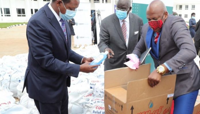 Shelter Afrique Chief Executive Officer Andrew Chimphondah (right) handing over food and sanitizers consignments to Governor of Machakos County Dr. Alfred Mutua (left), witnessed by Shelter Afrique's Board Chairman Steve Mainda. The relief food will support over 2,000 needy families in the county affected by the Coronavirus disease (Covid-19) pandemic.