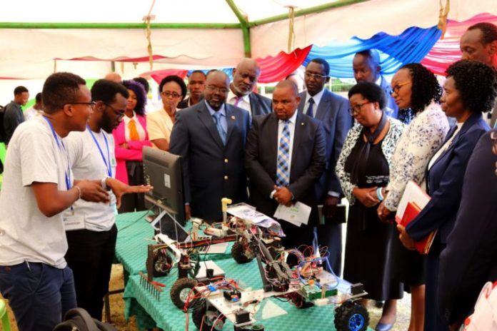 FILE PHOTO | Micheal (left) and Ken explain to the JKUAT Tech Expo guest how the weeding bot works scaled.